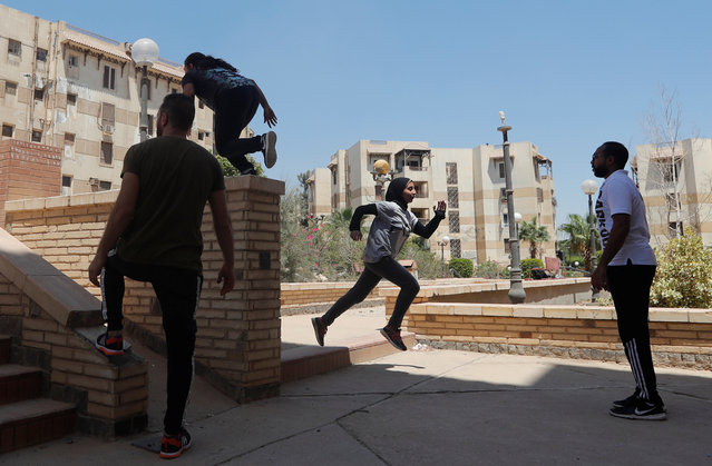 """Mohamed Omran, coach at Parkour Egypt """"PKE"""", watches his students' skills around buildings on the outskirts of Cairo, Egypt on July 20, 2018. Founded in France in the 1980s as the Art du Deplacement and later taking its name from the French word 'parcours' (course or route), Parkour involves running, climbing and jumping acrobatically around buildings and over terrain. (Photo by Amr Abdallah Dalsh/Reuters)"""