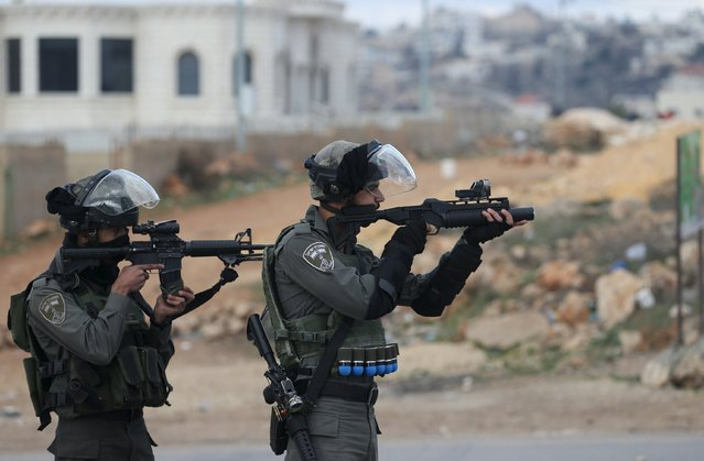 Israeli border policemen point their weapons at Palestinian protesters during clashes in the West Bank village of Silwad, near Ramallah December 26, 2015. (Photo by Mohamad Torokman/Reuters)