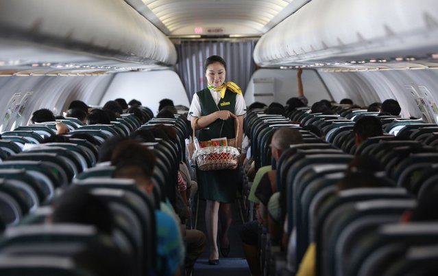 A Spring Airlines crew member sells food onboard an Airbus A320 aircraft near Shanghai in this July 6, 2012 file photo. A rush to buy into China's only listed low-cost carrier has sent Spring Airlines Co shares rocketing just as new arrivals herald the beginnings of a price war that could eat into already-low profit margins. (Photo by Aly Song/Reuters)