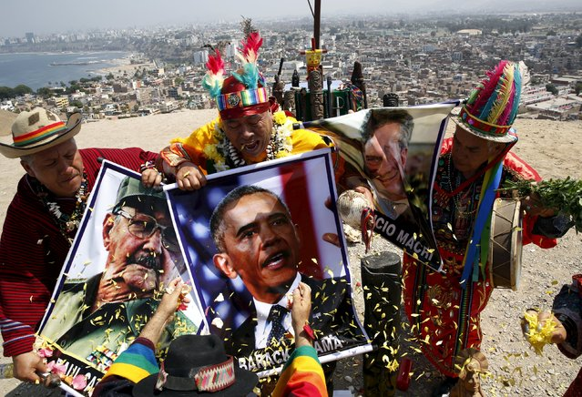 Peruvian shamans holding posters of Cuba's President Raul Castro, U.S. President Barack Obama and Argentinian President Mauricio Macri perform a ritual of predictions for the new year at Morro Solar hill in Chorrillos, Lima, Peru, December 29, 2015. (Photo by Mariana Bazo/Reuters)