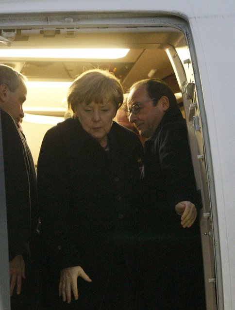 Germany's Chancellor Angela Merkel (C) and France's President Francois Hollande (R) walk out after a meeting inside a plane at an airport near Minsk, February 11, 2015. (Photo by Valentyn Ogirenko/Reuters)
