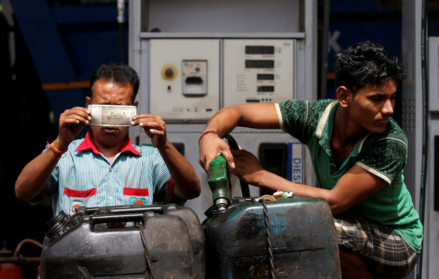 A worker checks a 500 Indian rupee note as a man fills diesel in containers at a fuel station in Kolkata, August 14, 2018. (Photo by Rupak De Chowdhuri/Reuters)