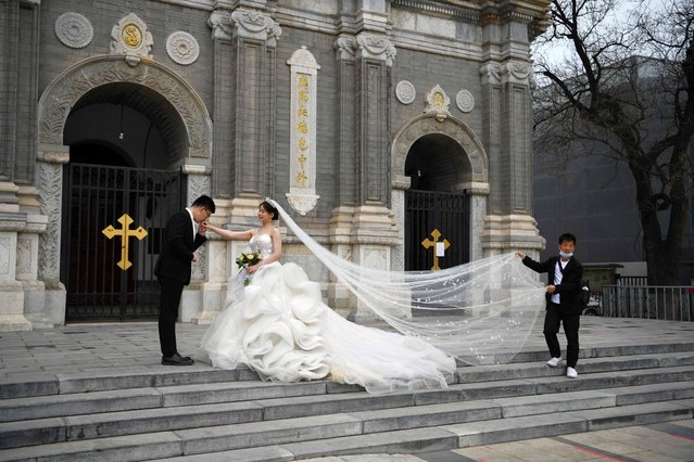 A couple poses for wedding photos outside St Joseph's Church, also known as Wangfujing Catholic Church, in Beijing on Easter Friday on April 2, 2021. (Photo by Greg Baker/AFP Photo)