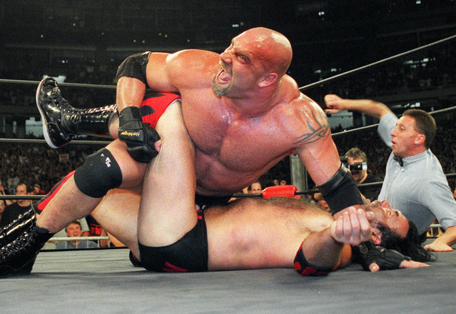 In this July 6, 1998, file photo, World Championship Wrestling heavyweight champion Bill Goldberg puts Scott Hall to the mat during a match in Atlanta. Bill Goldberg punched through the drywall in his garage one day this week – not as some sort of masochistic training for his next WWE match –  but for repairs on property damage suffered as a result of the deadly Texas storms. The WWE Hall of Famer spent about 12 hours Wednesday, Feb. 24, 2021 replacing pumps in the wells on the ranch he owns just outside San Antonio, and then it was off to work on a garage and pool house that had been flooded. (Photo by Erik S. Lesser/AP Photo/File)