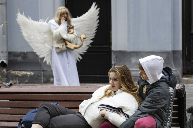 A young couple rest on a bench, as a street actor wearing an Angel costume speaks on the phone in Nikolskaya street near the Kremlin in Moscow, Russia, Wednesday, March 31, 2021. (Photo by Alexander Zemlianichenko/AP Photo)