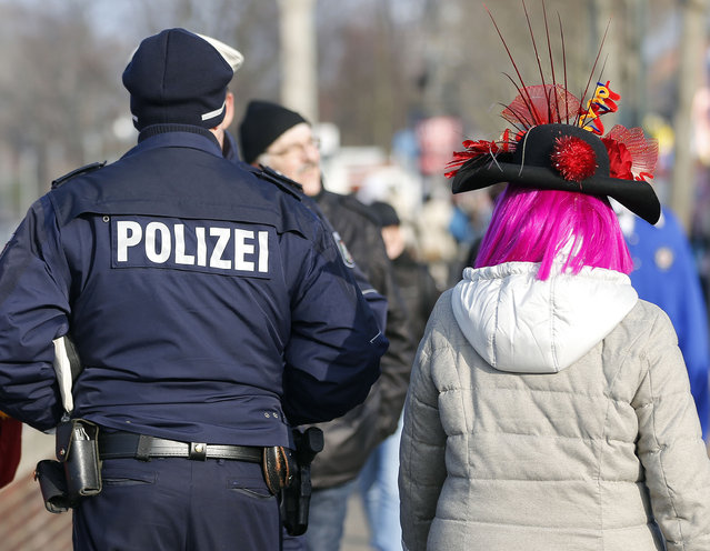 A reveller passes a police officer prior to the traditional Rose Monday carnival parade in Duesseldorf, Germany, Monday, February 16, 2015. (Photo by Frank Augstein/AP Photo)