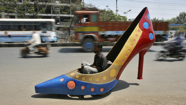 A worker test drives a car in the shape of a heels on a road in the southern Indian city of Hyderabad March 7, 2012. The shoe is part of a ladies series of creations by Indian car designer Sudhakar Yadav to mark the International Women's Day and the car can run at a maximum speed of 45 kph (28 mph). (Photo by Krishnendu Halder/Reuters)