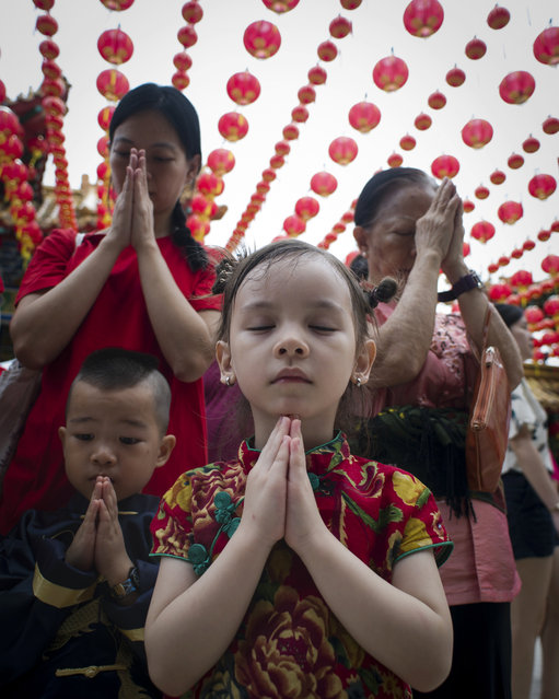 Visitors offer prayers on the first day of Chinese Lunar New Year at a temple in Kuala Lumpur, Malaysia on Thursday, February 19, 2015. (Photo by Joshua Paul/AP Photo)