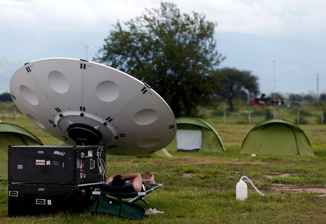 A man takes a nap under a TV satellite dish at the Dakar Rally 2016 in Salta, Argentina, January 10, 2016. (Photo by Marcos Brindicci/Reuters)