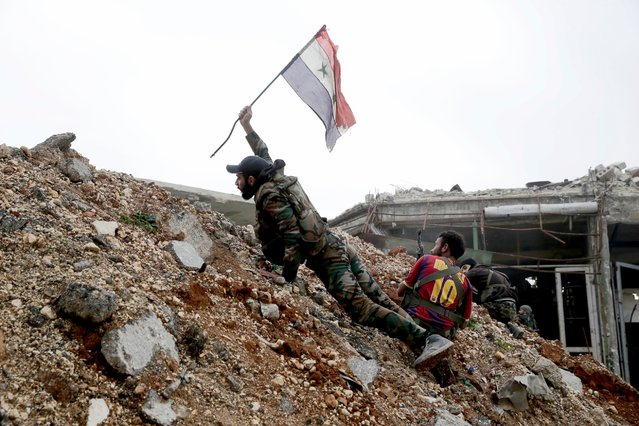 A Syrian army soldier places a Syrian national flag during a battle with rebel fighters at the Ramouseh front line, east of Aleppo, Syria, December 5, 2016. The fighting was most intense Monday near the dividing line between east and west Aleppo as government and allied troops push their way from the eastern flank. (Photo by Hassan Ammar/AP Photo)