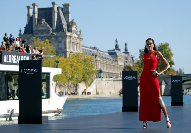 Model Winnie Harlow presents a creation on a giant catwalk installed on a barge on the Seine River during a public event organized by French cosmetics group L'Oreal as part of Paris Fashion Week, France, September 30, 2018. (Photo by Stephane Mahe/Reuters)