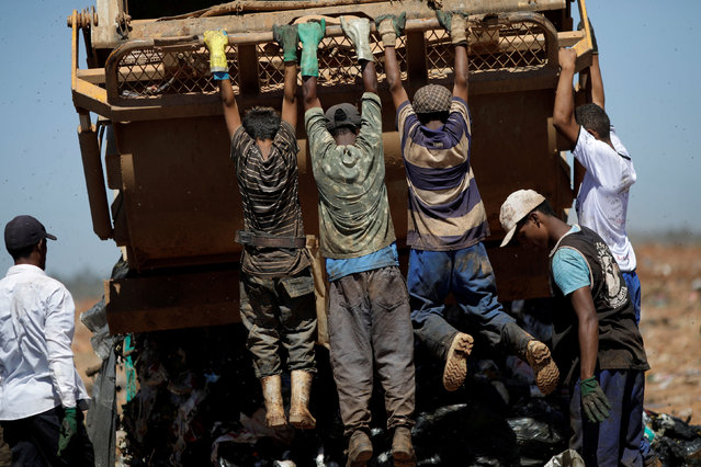 """Children hang from a garbage truck at """"Lixao da Estrutural"""", Latin America's largest rubbish dump, in Brasilia, Brazil, January 19, 2018. (Photo by Ueslei Marcelino/Reuters)"""