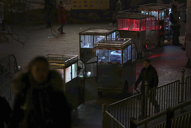 Commuters walk past tricycles parked for customers outside a subway station in Beijing, Tuesday, January 19, 2016. (Photo by Andy Wong/AP Photo)