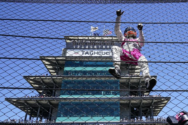 Helio Castroneves of Brazil climbs the fence at the start/finishing as he celebrates after winning the Indianapolis 500 auto race at Indianapolis Motor Speedway in Indianapolis, Monday, May 31, 2021. (Photo by Paul Sancya/AP Photo)