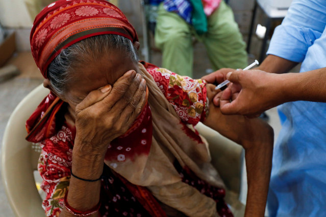 Basanti, 71, reacts as she receives a dose of the coronavirus disease (COVID-19) vaccine at a vaccination center in Karachi, Pakistan on June 9, 2021. (Photo by Akhtar Soomro/Reuters)