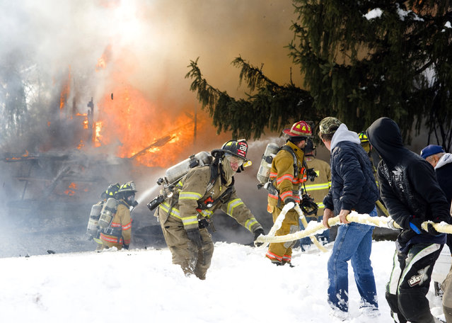 Firefighters and civilians stretch a line toward a burning house in Little Mahanoy Township, Pa., on Sunday, January 24, 2016. About a half mile of a private road needed to be plowed open to access the burning house, which ended up being a total loss. (Photo by Larry Deklinski/The News-Item via AP Photo)