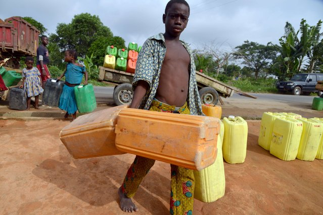 A boy arrives with jerrycans to fetch water in Abobo, a suburb of Abidjan, on March 20, 2015. Without reforms, the world will be plunged into a water crisis that could be crippling for hot, dry countries, the United Nations has warned. (Photo by Issouf Sanogo/AFP Photo)
