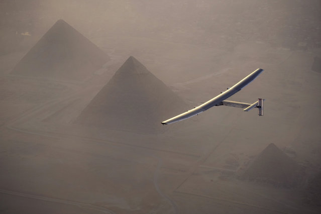 This handout photo released by Solar Impulse 2 shows the solar powered plane, piloted by Swiss pioneer André Borschberg, during the flyover of the pyramids of Giza on July 13, 2016 prior to landing in Cairo, Egypt. The 16th leg of the round-the-world-trip from Seville in Spain covered a distance of 3,700 kilometers and took almost 49 hours. The Solar Impulse 2 landed in Cairo on July 13, 2016  for the penultimate stop in the solar-powered plane's world tour, two days after setting off from Spain. The 16th leg of the round-the-world-trip from Seville in Spain covered a distance of 3,700 kilometers and took almost 49 hours. (Photo by Jean Revillard/AFP Photo/Solar Impulse 2)