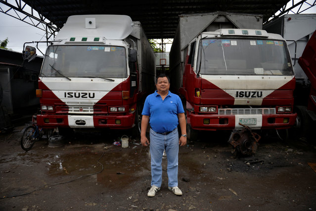 """Jose Cecilia Jr., 51, poses for a photograph in front of trucks at a trucking company he owns in Santa Rosa, Laguna, south of Manila, Philippines December 2, 2016. """"I give one hundred percent for Duterte. He's the only president who is fighting the drug lords and other syndicates in our country"""", he said. (Photo by Ezra Acayan/Reuters)"""