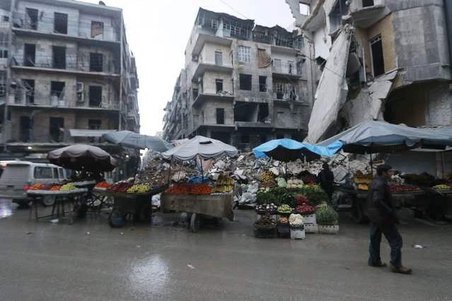 Fruits and vegetables are displayed for sale in front of damaged buildings in the rebel-held area of Aleppo's al-Shaar neighbourhood January 2, 2015. (Photo by Hosam Katan/Reuters)