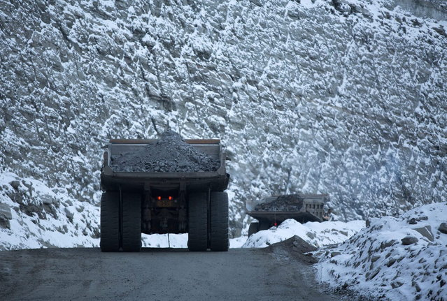 Dump trucks carry diamond ore away from the base of the open pit at the Udachny diamond mine operated by OAO Alrosa in Udachny, Russia, on Sunday, November 17, 2013. (Photo by Andrey Rudakov/Bloomberg)