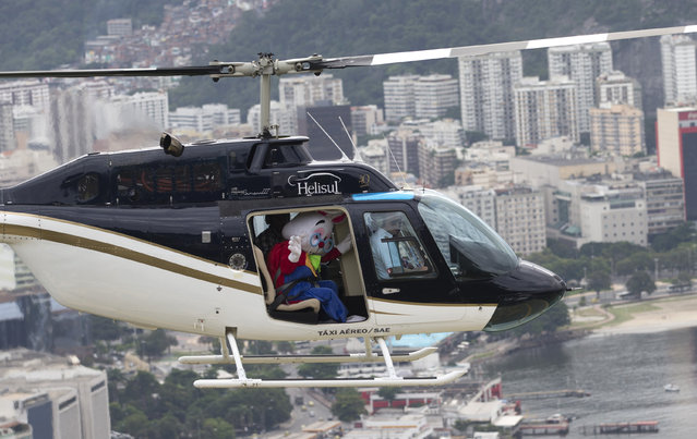 A man dressed as the Easter Bunny waves from an helicopter as he arrives to Urca Hill in Rio de Janeiro, Brazil, Wednesday, April 1, 2015. The Easter Bunny arrived for an event with children. (Photo by Silvia Izquierdo/AP Photo)