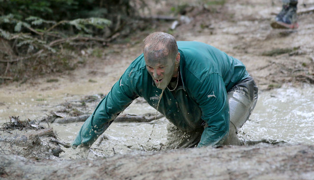 A participant of the Wild Sau Dirt Run 2015 passes a mud  hole in Obertriesting, Lower Austria, Austria, Saturday, April 4, 2015. (Photo by Ronald Zak/AP Photo)