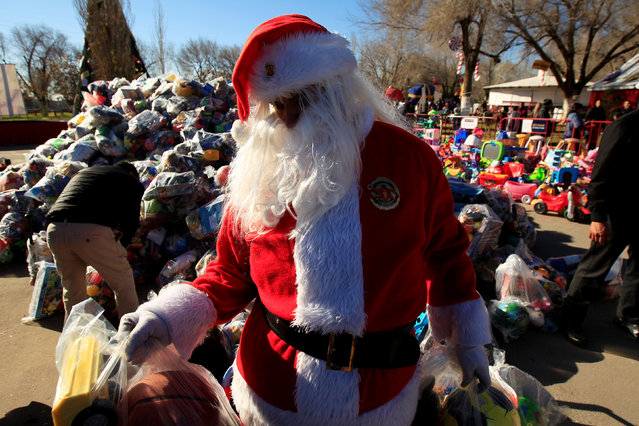 A firefighter dressed as Santa Claus is seen during the annual gift-giving event organized by the Fire Department, in which they hand out items donated throughout the year to children in need, in Ciudad Juarez, Mexico, December 24, 2018. (Photo by Jose Luis Gonzalez/Reuters)