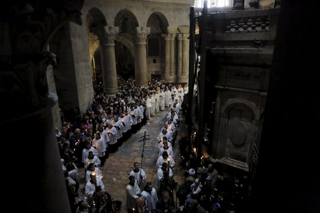 Members of the Catholic clergy and Christian worshippers hold candles during Easter procession in the Church of the Holy Sepulchre in Jerusalem's Old City April 5, 2015. (Photo by Ammar Awad/Reuters)