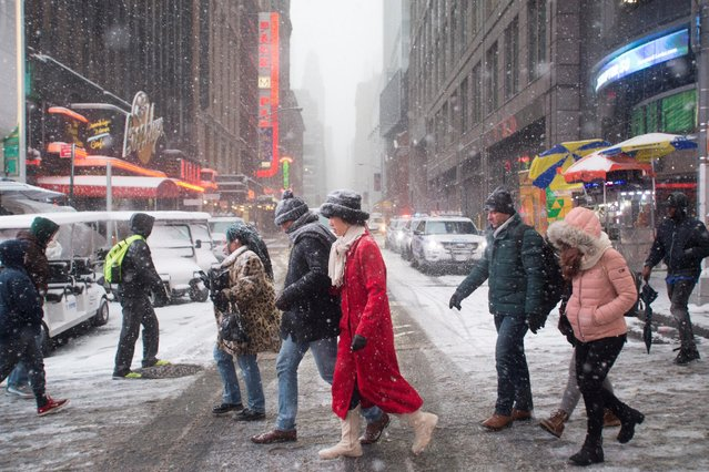 People brave the cold on a snowy day in Times Square in New York City, U.S., January 7, 2017. (Photo by Alex Wroblewski/Reuters)