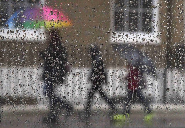 A family is seen through raindrops on a window as they shelter under umbrellas during a rainstorm in London, February 16, 2015. (Photo by Neil Hall/Reuters)