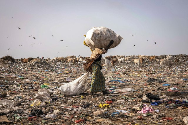 A waste picker walks with a load of recyclable waste on her head in the Mbeubeuss rubbish dump in Dakar on July 14, 2021. Almost all of it ends up in Mbeubeuss, a landfill about 30 kilometres (18 miles) from the centre which has a notorious reputation as an environmental hazard. Pickers set fire to the rubbish to find valuable metals, for example, spewing noxious fumes onto neighbouring residential areas. (Photo by John Wessels/AFP Photo)