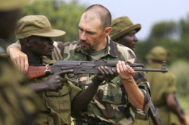 Former French special forces arms instructor Norbert Tible teaches a Congolese park ranger the use of an AK-47 assault rifle July 21, 2006 at Ishango in the Virunga National Park in eastern Democratic Republic of Congo. (Photo by John Moore/Getty Images)