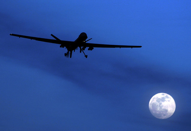 In this January 31, 2010, file photo, an unmanned U.S. Predator drone flies over Kandahar Air Field, southern Afghanistan on a moonlit night. (Photo by Kirsty Wigglesworth/AP Photo)