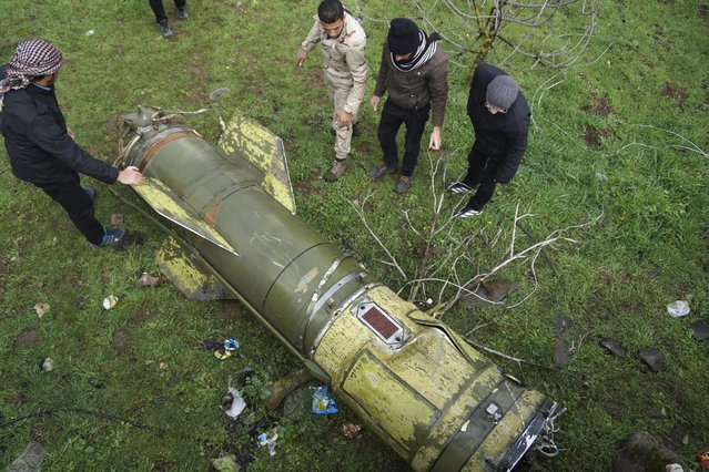 Rebel fighters inspect a piece of a rocket that landed in an area that connects the northern countryside of Deraa and Quneitra countryside, Syria February 22, 2016. (Photo by Alaa Al-Faqir/Reuters)