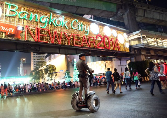 A Thai police officer patrols as people start to gather on a street outside the Central World shopping mall to celebrate the New Year in Bangkok, Thailand, Tuesday, December 31, 2013. (Photo by Apichart Weerawong/AP Photo)