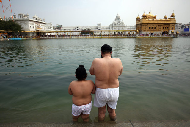 """A Sikh man and his son pray before taking a holy dip in the """"Sarowar"""", or sacred pond, of the Golden Temple, the holiest shrines of the Sikhs, on the occasion of the Visakhi festival, in Amritsar, India, 14 April 2015. On Visakhi Day of 1699 A.D. Guru Gobind Singh ji, the tenth Sikh Master organized the Sikhs under one order called the """"Khalsa Panth"""". The Visakhi festival also marks the beginning of the Sikh New Year. (Photo by Raminder Pal Singh/EPA)"""