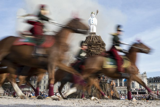 """In this April 13, 2015 photo members of a guild ride around the """"Boeoegg"""" on the Sechselaeuten place in Zurich, Switzerland. The Sechselaeuten (ringing of the six o'clock bells) is a traditional end of winter festival with a parade of guilds in historical uniforms on horseback and the burning of the Boeoegg, a symbolic snowman. The faster the Boeoegg explodes, the hotter the summer will be according to traditional weather rules. (Photo by Ennio Leanza/Keystone via AP)"""