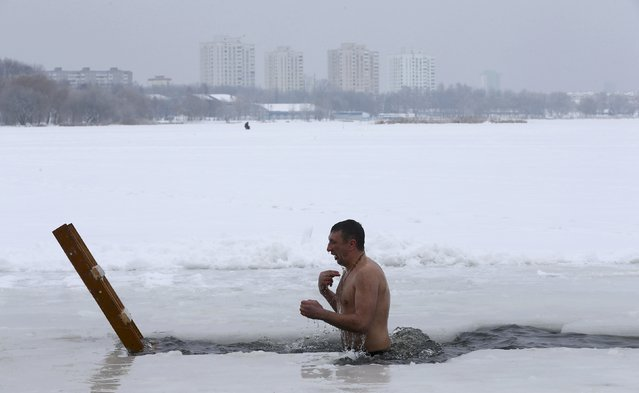 A man takes a dip in icy waters of a lake during Orthodox Epiphany celebrations in Minsk, Belarus January 19, 2017. (Photo by Vasily Fedosenko/Reuters)
