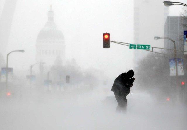 A person struggles to cross a street in blowing and falling snow as the Gateway Arch appears in the distance Sunday, January 5, 2014, in St. Louis. Snow that began in parts of Missouri Saturday night picked up intensity after dawn Sunday with several inches of snow on the ground by midmorning and more on the way. (Photo by Jeff Roberson/AP Photo)