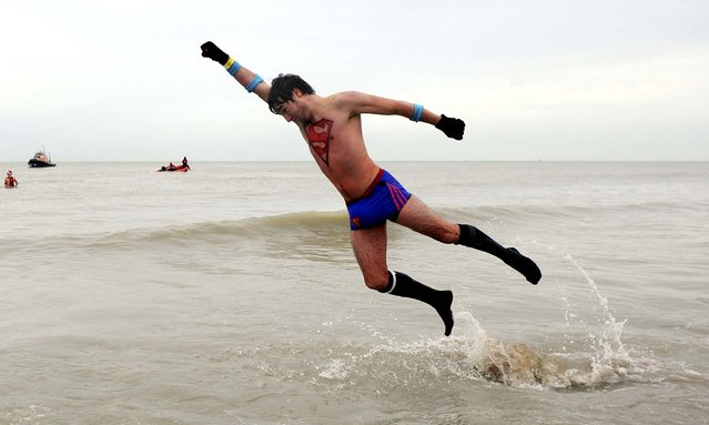 A man dressed to look like Superman plays in the water as people take their first bath in the North Sea to celebrate the arrival of the new year, in Ostende, Belgium, on January 4, 2014. (Photo by Laurent Dubrule/Reuters)