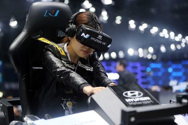 A visitor tries out a Hyundai virtual reality simulator at the 16th Shanghai International Automobile Industry Exhibition in Shanghai, China, 20 April 2015. (Photo by How Hwee Young/EPA)
