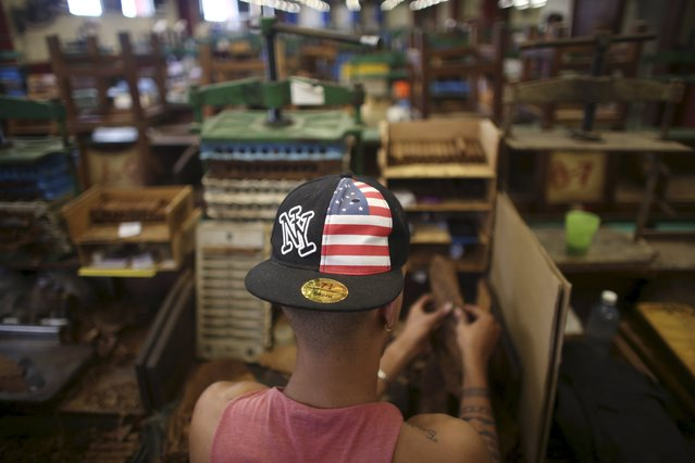 A worker wearing a cap with the colours of the U.S. flag rolls tobacco at the Corona Tobacco factory in Havana, March 3, 2016. (Photo by Alexandre Meneghini/Reuters)