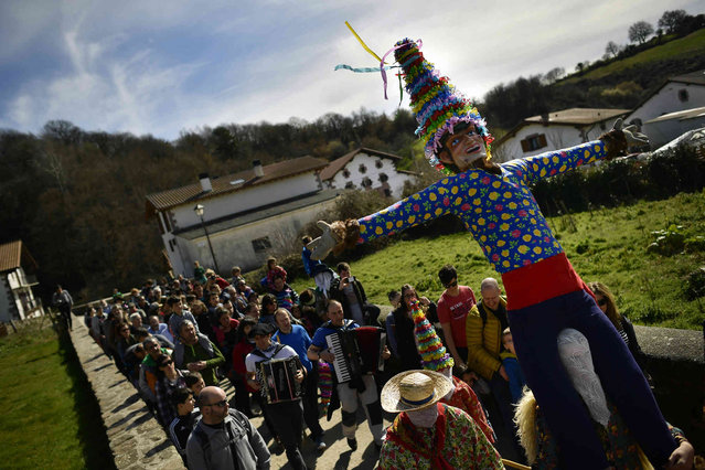 "People carry a giant ""Miel Otxin""', the symbol of the carnival, during an ancient rural carnival in the small Pyrenees village of Lantz, northern Spain, Sunday, March 3, 2019. The carnival is a long-standing rural tradition in which the forces of good and evil confront each other in a symbolic battle. From Sunday to Tuesday, during carnival week, in the little village of Lantz, the legendarily evil bandit ""Miel Otxin"", represented by a doll filled with straw, is imprisoned and sentenced to death by fire. (Photo by Alvaro Barrientos/AP Photo)"