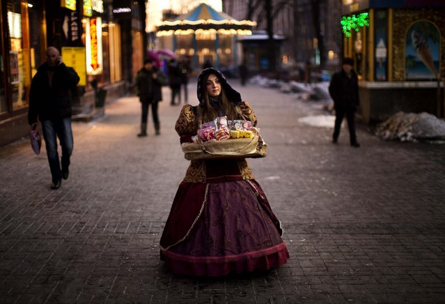 A woman sells candies in a street heading to Kiev's Independence Square, the epicenter of the country's current unrest, Ukraine, Tuesday, February 4, 2014. Ukrainian opposition leader Vitali Klitschko, after meeting with the country's beleaguered president, is warning that tempers are heating up and says the president must take action to resolve the country's political crisis. (Emilio Morenatti/Associated Press)
