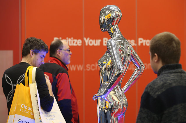 Visitors walk past a metallic mannequin at the 2016 CeBIT digital technology trade fair on the fair's opening day on March 14, 2016 in Hanover, Germany. The 2016 CeBIT will run from March 14-18. (Photo by Sean Gallup/Getty Images)