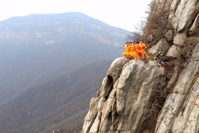 Students from a martial arts school practice Shaolin Kung Fu on cliffs at Songshan Mountain in Dengfeng, Henan Province, China, March 17, 2016. (Photo by Reuters/China Daily)