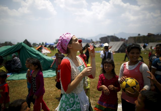 A medical clown blows soap bubbles in front of children affected by the April 25 earthquake in Kathmandu May 6, 2015. A team of five medical clowns from Israel is visiting earthquake victims to ease trauma effects and to reduce pain and anxiety among children and adults in communities and hospitals via their clowning skills. (Photo by Navesh Chitrakar/Reuters)