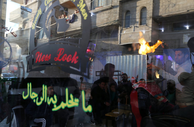 Palestinian barber Ramadan Odwan is pictured through a glass window as he styles and straightens the hair of a customer with fire, at his salon in Rafah in the southern Gaza Strip February 2, 2017. (Photo by Ibraheem Abu Mustafa/Reuters)