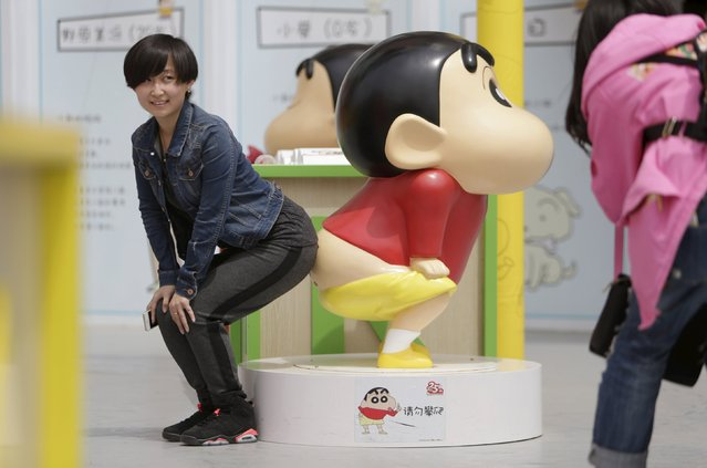 A visitor poses for a photo with a Crayon Shin-chan model during an exhibition at Joy City in Beijing May 5, 2015. (Photo by Jason Lee/Reuters)